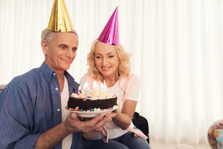 Birthday of the elderly person. People in a birthday hats. Elderly people celebrate birthday.