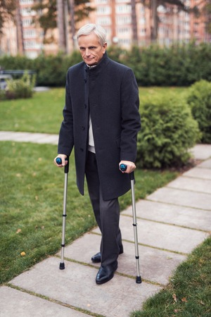 An elderly man walks with walkers for adults. An elderly man on a walk in the park.