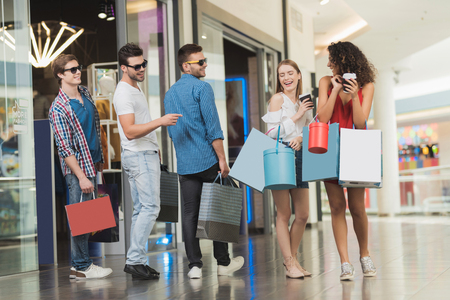 Verkoop in Black Friday. Het gezelschap van jonge mensen houdt zich bezig met winkelen op een zwarte vrijdag. Stockfoto