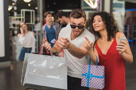 The girl and her boyfriend are shopping at the mall. Sale on a black Friday. A young couple are shopping.