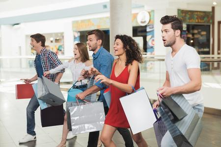 Uitverkoop in Black Friday. Het gezelschap van jongeren houdt zich bezig met winkelen op een zwarte vrijdag.