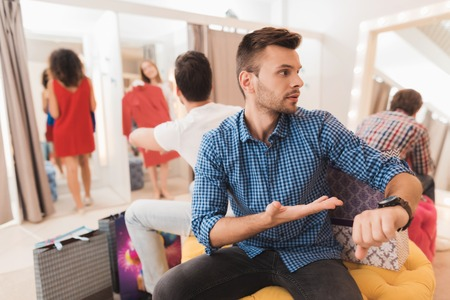 Man in the dressing room is waiting for his girlfriend. Girl tries on things in the fitting room.