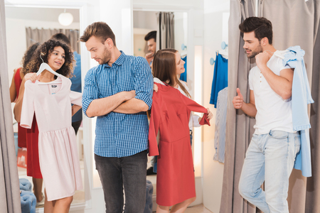 Men in the fitting room are waiting for their girls. Girls trying on things in the fitting room. Stok Fotoğraf