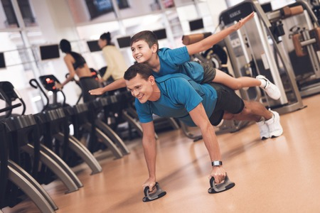 Dad and son in the same clothes in gym. Father and son lead a healthy lifestyle. Archivio Fotografico