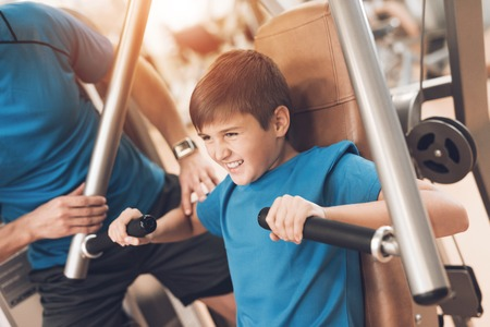 Dad and son in the same clothes in gym. Father and son lead a healthy lifestyle. Banque d'images