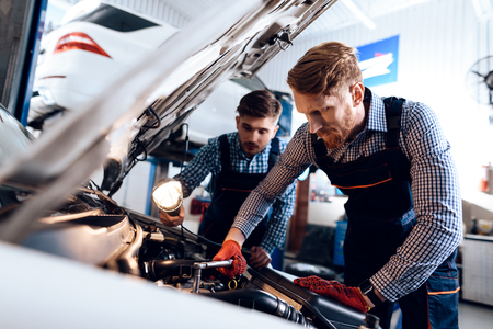 Father and son work at the auto service. Two mechanics work with the details of the car. Stock Photo