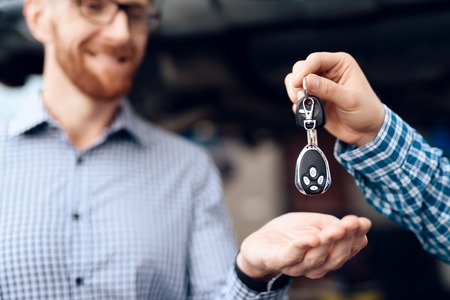 The man takes his car from the auto service. The mechanic transfers the car keys to the customer