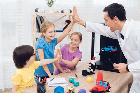 The teacher tells the children during the lesson how the 3D printer works. Foto de archivo