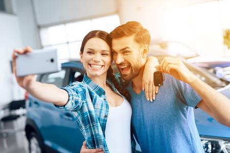 Un homme et une femme font un selfie près de leur nouvelle voiture.