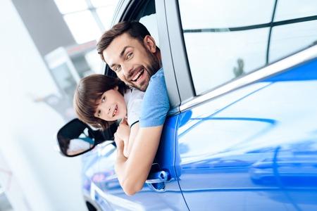 Een man met een kleine zoon zit achter het stuur van de auto.