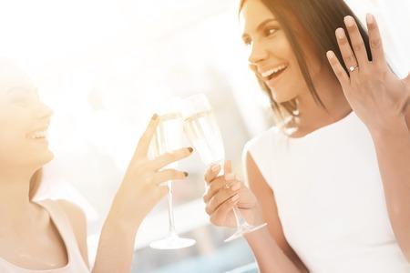 結婚前のケア。編パーティーで女の子。彼らはシャンパン グラスでソファに座っています。