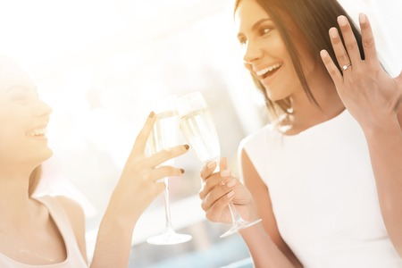 Pre-bruiloft zorg. Meisjes op een vrijgezellenfeest. Ze zitten op de bank met een glas champagne. Stockfoto