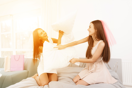 Pre-wedding care. Girls at a hen-party are having pillow fight on the bed. They have fun in a bright room.