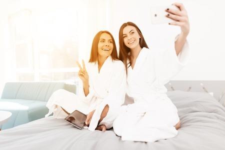 소녀들은 암탉 파티에서 즐거운 시간을 보낸다. 흰 가운에 갈색 머리는 밝은 방에서 재미 있습니다.