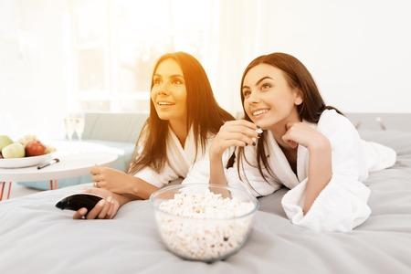 女の子はめんどりパーティーで楽しい時間を過ごします。白いバスローブのブルネットは明るい部屋で楽しいです。 写真素材