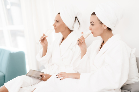 Girls have a great time at the hen-party. Brunettes in white bathrobes have fun in a bright room.