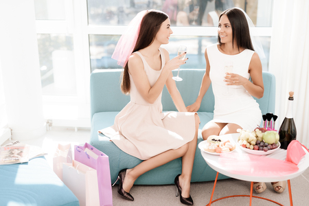 Pre-wedding care. Girls at a hen-party. They sit on the couch with a glass of champagne. Banco de Imagens - 91433472