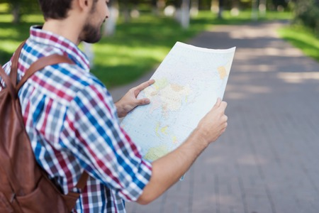 Close up. A man holds in his hands an expanded map of the world. He thinks where to go next. Reklamní fotografie