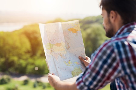 A man holds in his hands an expanded map of the world. He thinks where to go next. Stock Photo