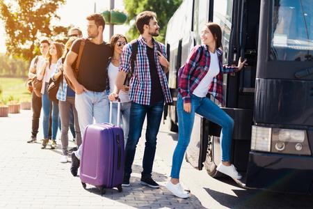 Un groupe de touristes s'apprêtant à monter dans le bus. Le gars avec la fille monte dans le bus et apporte ses bagages. Banque d'images - 97780709