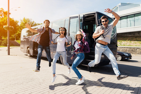 Four tourists jumped for posing in the photo. They are having fun. They stretched out their hands and smiled. Imagens - 97780727