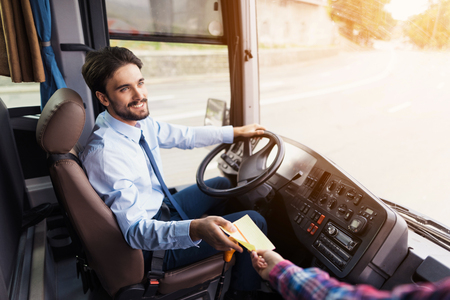The driver of the tourist bus is smiling and looking at the camera. The passenger gives him a ticket for the bus ride.