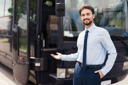 A male driver smiling and posing against a black tourist bus. Behind the back is a modern black tourist bus.