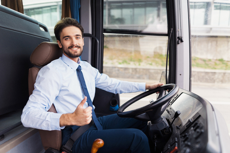 The driver of the tourist bus is smiling and looking at the camera. Archivio Fotografico