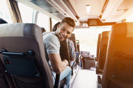 The guy is on the bus. He turned and looked at the passenger who was sitting behind him. The guy is smiling. Banco de Imagens - 97780920
