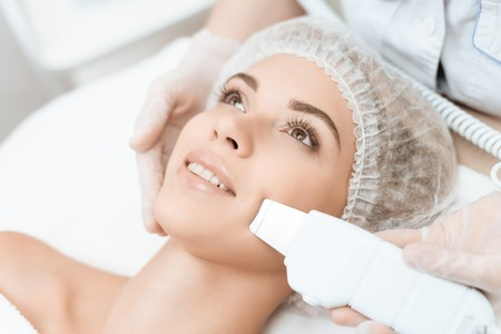 The doctor cleanses the womans skin with a special medical device. The woman came to procedure of laser hair removal.
