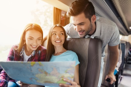 Tourists look at the map and choose where to go next. They discuss the upcoming journey and smile. Standard-Bild