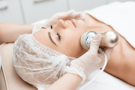The doctor drives the girl in the face of the photoepilator. The girl came to the procedure for laser hair removal.