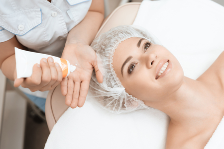 Doctor puts on hands a special cream for massage. She treats the skin of face of the girl who came to the beauty salon.