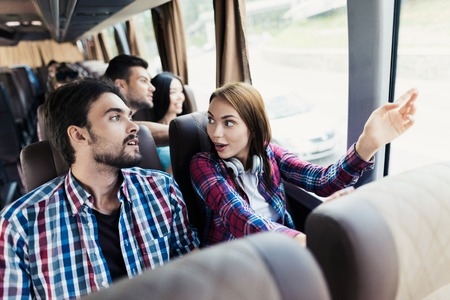 The guy and the girl are on the bus. The girl has headphones. He and the guy are discussing something and smiling.