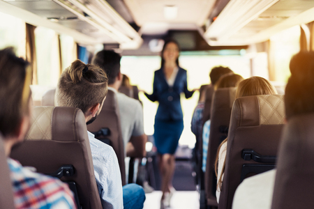 A stewardess is posing on the bus. It stands between the rows of seats on which passengers are sitting.