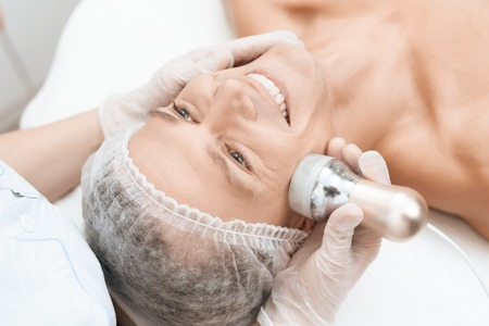 The doctor treats the male skin with a photoepilator. The man is lying on the couch and is smiling. Standard-Bild
