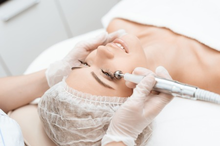 The doctor treats the girls face with a photoepilator. Doctor treats the girls skin around the eyes. Standard-Bild