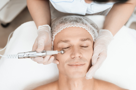 A man came to laser hair removal facial. Doctor leads him in the face with a modern laser epilator.