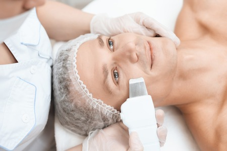 The doctor cleans the skin of a man with a special medical device. The man is lying on the couch of modern beauty salon.