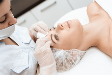 The doctor makes the girl a facial cleansing massage. The girl came to the procedure of laser hair removal.