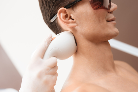 The man came to procedure of laser hair removal. The doctor treats his shoulders, neck and back with a special apparatus Standard-Bild