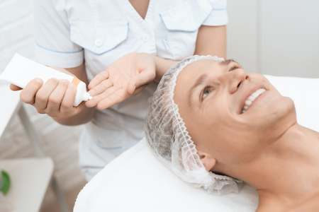 The doctor squeezes a special cream on his hands after laser hair removal.