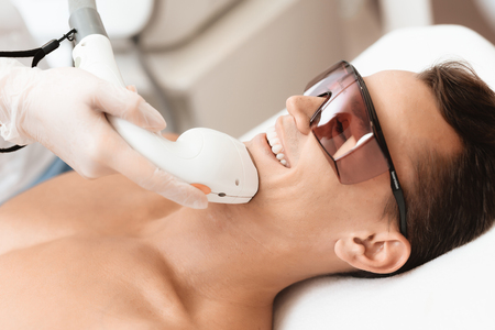 The man came to the procedure of laser hair removal. The doctor treats his neck and face with a special apparatus.
