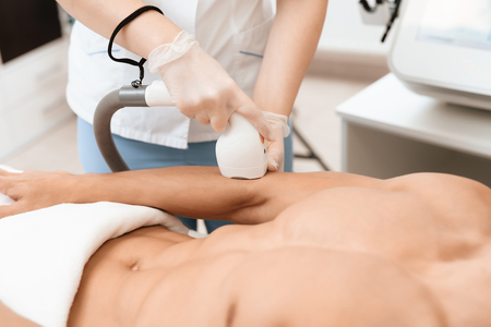 The man came to the procedure of laser hair removal. The doctor treats his hands with a special apparatus.