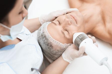The doctor treats the skin of a man with a modern photoepilator. Standard-Bild