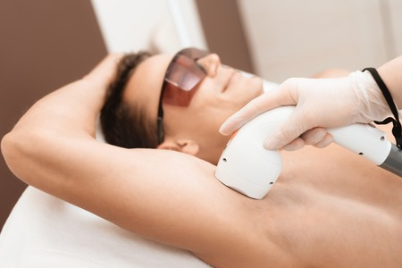The man came to the procedure of laser hair removal. The doctor treats his armpit with a special apparatus.