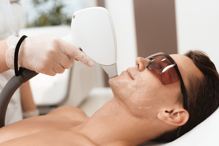 The doctor treats the face of a man with a modern laser epilator. The man lies and smiles.