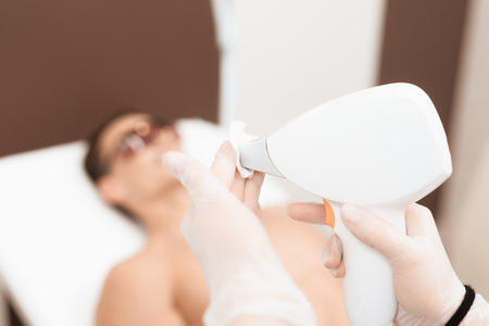 The doctor is preparing a laser hair removal machine. Against the background is the man who will be given procedure.