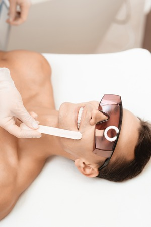 The doctor applies an epilation gel on the mans face. The man laughs, because he is ticklish.