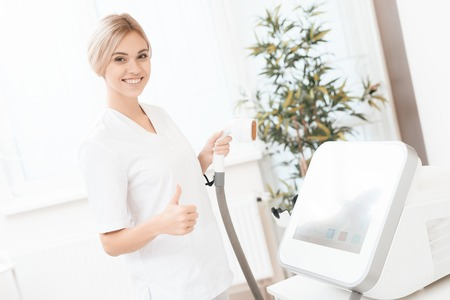 A woman tunes a laser hair removal machine. She holds a working part of the epilator in her hands and poses for a photo. Stockfoto